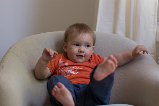 Horizontal full length portrait of cute fair toddler girl in orange shirt and blue pants wiggling in armchair with adorable funny expression