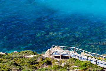Wall Mural - Wooden footbridge on the coast along the sea with clear transparent water