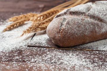 Whole loaf of dark homemade bread sprinkled with flour near bunch of wheat lies on old brown boards