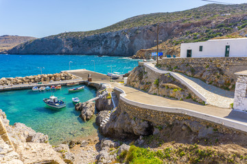 Potamos village with the port and the colorful fishing boats sailing in the turquoise sea waters in Antikythera island in Greece