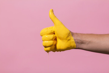 """male hand showing sign thumb up with paint flowing down on a colored background. creative idea, creative concept, gesture """"class"""""""