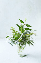 Bouquet of green tree branches (eucalyptus, wild olive) and yellow flowers in glass vase