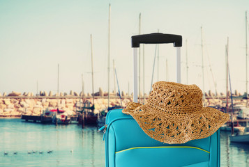 Wall Mural - holidays. travel concept. blue suitcase infront of marina background