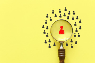 business image of magnifying glass with people icon over yellow background, building a strong team, human resources and management concept