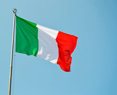 Italian national flag vawing in the wind with blue sky used as background
