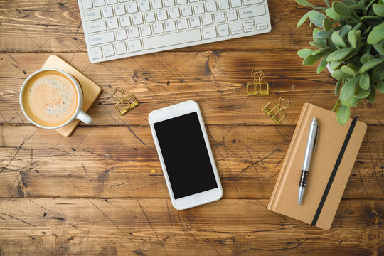 Smartphone mockup template with coffee cup and notebook on wooden table. Top view from above