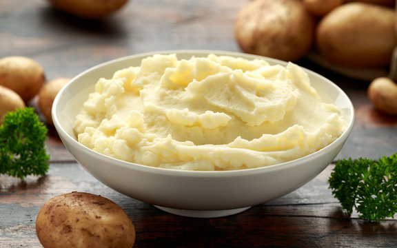 Mashed potatoes in white bowl on wooden rustic table. Healthy food