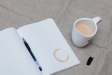 refiner from a cup of coffee on the notebook with open gel pen and cup of milk cofee on the flax backgruond on the table