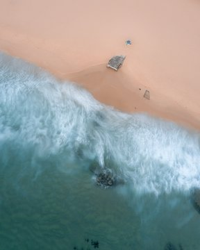 Aerial shot of the coast with splashing waves covering a sandy beach