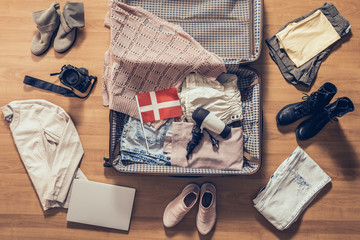 Woman's clothes, laptop, camera and flag of Denmark lying on the parquet floor near and in the open suitcase. Travel concept