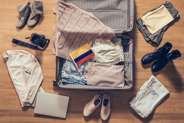 Woman's clothes, laptop, camera and flag of Colombia  lying on the parquet floor near and in the open suitcase. Travel concept