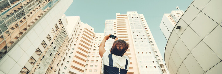 A girl is taking pictures of a new residential complex. White modern skyscrapers. New housing
