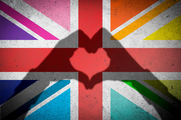 Hands making heart shadow on Union Jack UK flag with LGBTQI gay pride rainbow colored panels on a textured grunge concrete wall background Fototapete