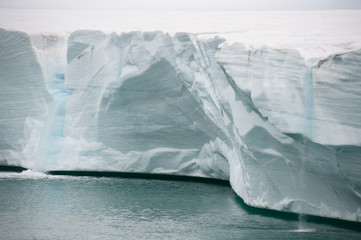 Close view from sea of two waterfalls cascading over a glacier wall caused by ice melting - Image