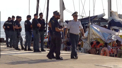 A still image from a video footage shows police officers guarding a migrant rescue boat, which docked at the port of Lampedusa in defiance of a ban on entering Italian waters, in Lampedusa