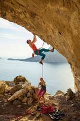 Young man starts climbing challenging route, his female partner belaying him