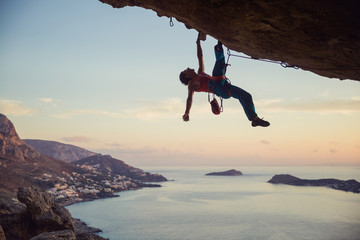 Young man struggling to climb challenging route on cliff