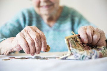 Detailed closeup photo of elderly 96 years old womans hands counting remaining coins from pension in her wallet after paying bills. Unsustainability of social transfers and pension system.