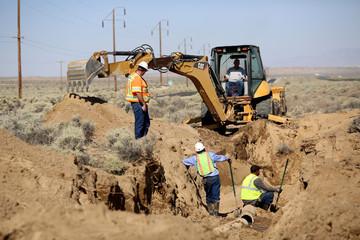 Workers dig up a broken water pipe near newly ruptured ground along Highway 178 after an earthquake broke, triggered by a previous day quake, in Southern California, east of the city of Ridgecrest