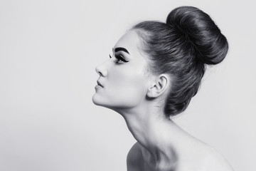 Vintage style black and white profile of young beautiful girl with fancy hair bun