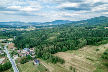 Mountains and green forest. Blue sky with clouds. Aerial shot.