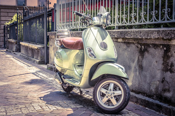 Scooter parked on an old street. Scooter or motorbike is one of the most popular transport in Europe. Vintage style photo. City scene with green retro scooter in summer.