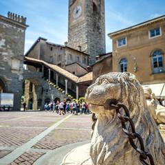 Fototapete - Piazza Vecchia in Citta Alta, Bergamo, Italy. Ancient architecture of Old town or Upper City in Bergamo. Stone lion is a decoration of vintage fountain in the ancient Bergamo center in summer.