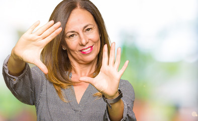 Beautiful middle age business woman Smiling doing frame using hands palms and fingers, camera perspective