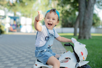 Little preschool kid boy driving orange motorbike toy at home. Child playing with green trees background. Copy space. Learning Concept.