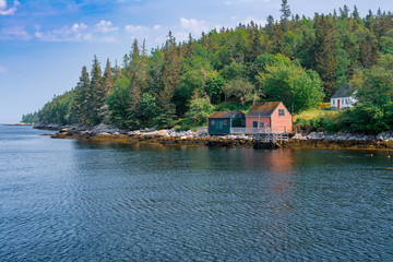 Rugged beauty of Nova Scotia's rural coast, scenic view of  houses and a shed along the rugged rural coast of Nova Scotia and the Atlantic Ocean.