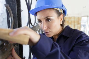female builder sanding metal fence