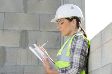 woman builder holding blueprints clipboard