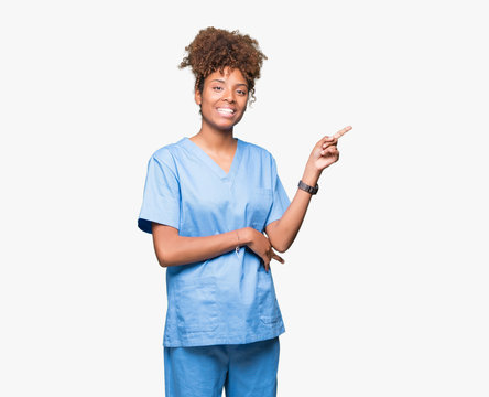 Young african american doctor woman over isolated background with a big smile on face, pointing with hand and finger to the side looking at the camera.
