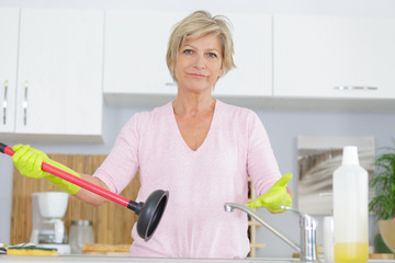 a senior woman with plunger