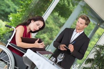 disabled customer giving male waiter her restaurant order
