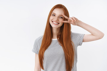 Waist-up shot friendly kind optimistic attractive young lucky teenage redhead girl blue eyes tilting head smiling white teeth show victory peace gesture enjoy party, standing white background