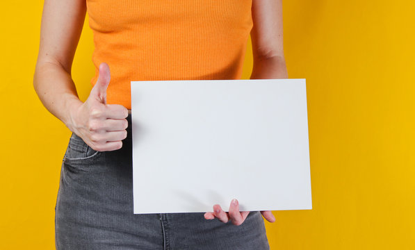 Woman holding white empty sheet of paper for copy space on yellow background. Crop photo, studio shot
