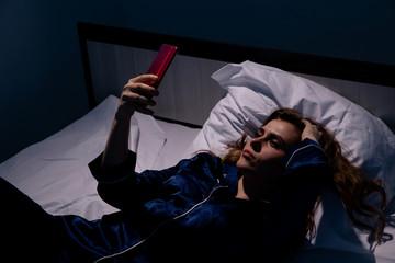 Upset woman lying in bed in sleepless