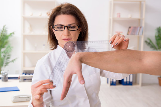 Female doctor checking patient's joint flexibility with goniometer