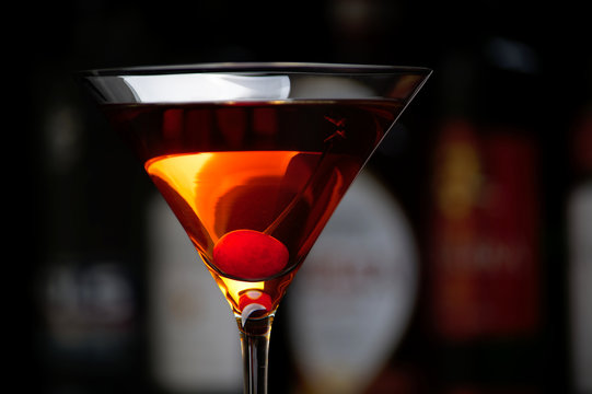 Manhattan drink with cherry with bar in the background