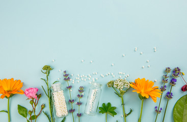 Flat lay view homeopathic medicine pills in jars and spilled around on light blue background, decorated with fresh various herbs and plants, flowers. Homeopathy border background, lot of copy space. Wall mural