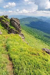 path through the edge of a mountain. beautiful summer landscape in mountains. big rock on the grassy slope in front. sunny weather with clouds on the sky
