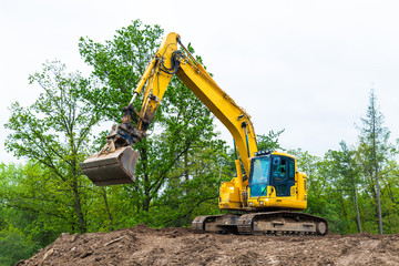Yellow belt excavator on construction site. Hydraulic earth mover. Backhoe loader. Rotating operator cabin, shovel and continuous tracks. Pile of soil, spring sky, green tree tops. Building industry.