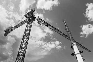 Tower crane installation. Black and white silhouette. Work at heights. Artistic construction background with sky and clouds. Telescopic boom of lifting device. Occupational safety. Building industry.