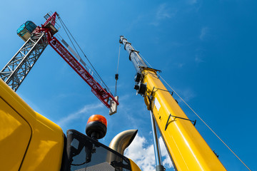 Tower crane assembly. Lifting device installation. Construction site. Placing a concrete counterweight by high telescopic boom of yellow mobile hoist machine. Blue sky. Bottom view. Building industry.