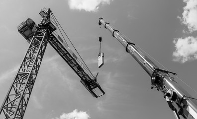 Tower crane assembly. Concrete counterweight installation. Artistic black and white skyline. Erecting of lifting device construction. High telescopic boom of a mobile hoist machine. Civil engineering.