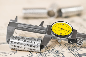 Caliper detail. Linear ball bearings and measuring tool on a technical document. Analog gauge with round yellow dial and vernier scale. Project drafting. Industrial repairing service. Education study.