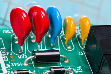 Colorful varistors. Circuit board detail. Electronic components for surge protector. Diodes, red, blue and yellow voltage-dependent resistors on green PCB from dismantled uninterruptible power supply.