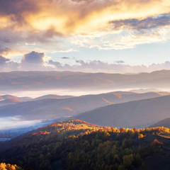 sunrise in mountains. beautiful autumn landscape with fog in the valley. ridge in the distance view from the hill. cloudy glowing sky.