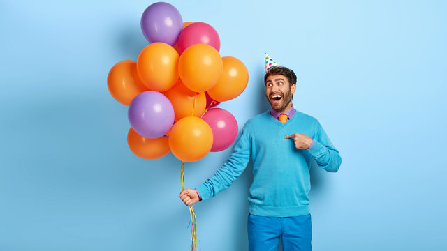 Lets have fun. Handsome happy man groom points at himeself, has party before wedding, good mood, stands with airballoons, has awesome day, wears blue outfit, poses indoor. Happiness concept.